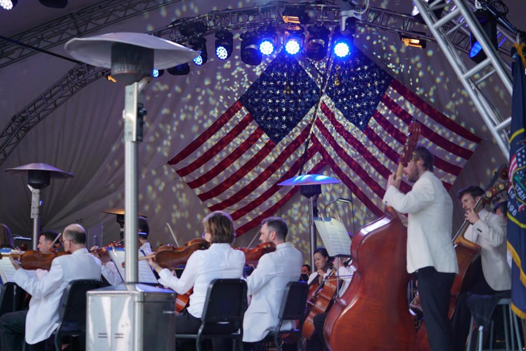 Orchestra playing outdoors with United States flags in background